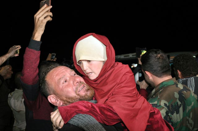 A man holds a young girl rescued from the Islamic State group