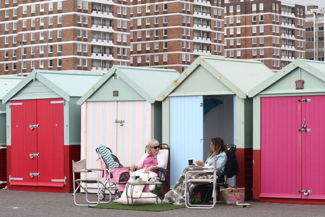 Ladies enjoy a beach hut at Brighton beach, East Sussex