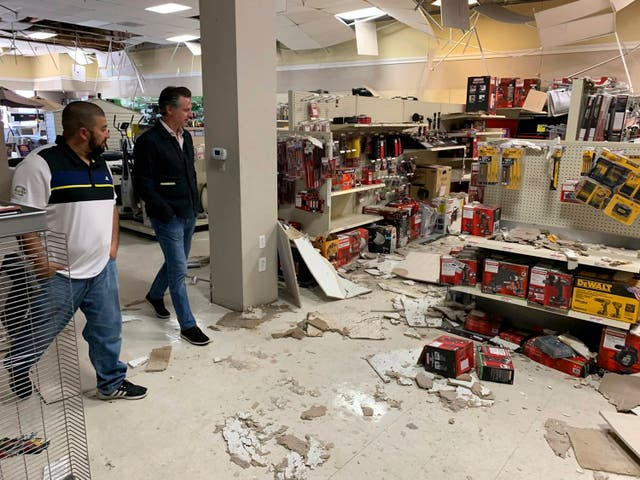 Gavin Newson, right, tours earthquake damage inside a shop  in Ridgecrest