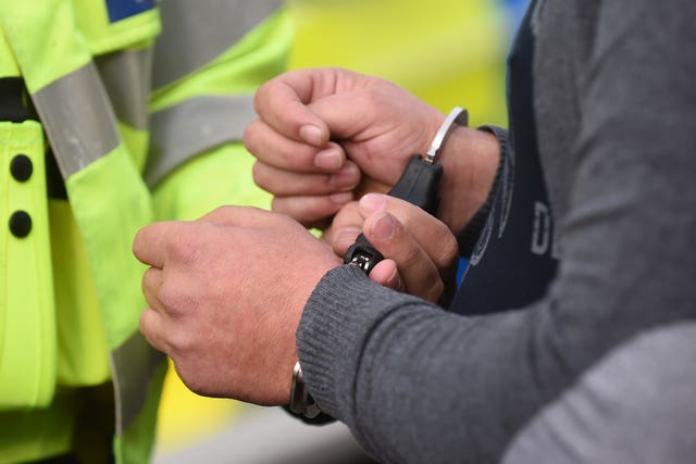 A man being placed in handcuffs