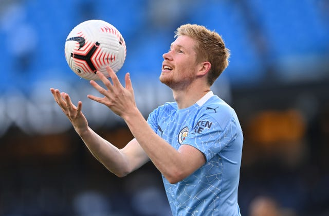 Manchester City midfielder Kevin De Bruyne tosses the ball in the air