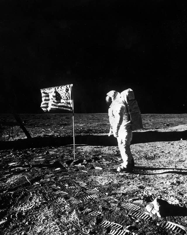 Buzz Aldrin with the US flag planted in the surface of the moon (PA)
