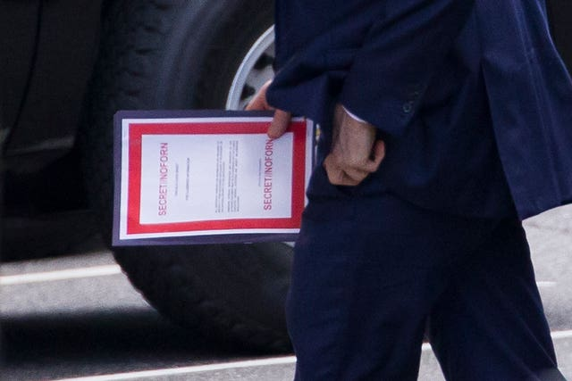 Acting defence secretary Patrick Shanahan carries a document labelled secret as he arrives for a meeting with President Donald Trump about Iran at the White House