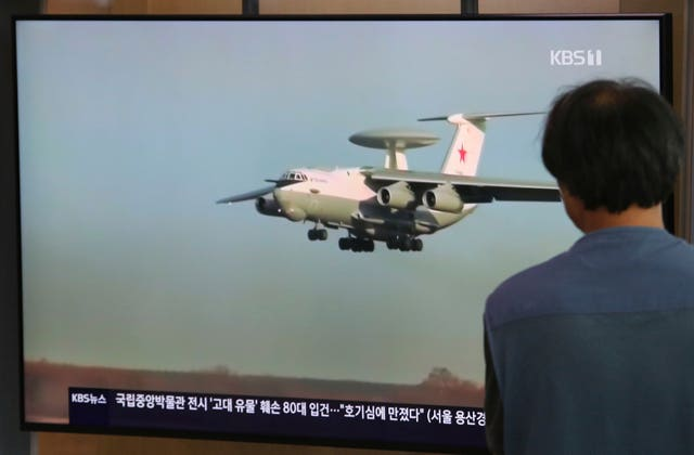 A man watches a TV showing a file image of Russian A-50 airborne early warning and control aircraft during a news programme at the railway station in Seoul