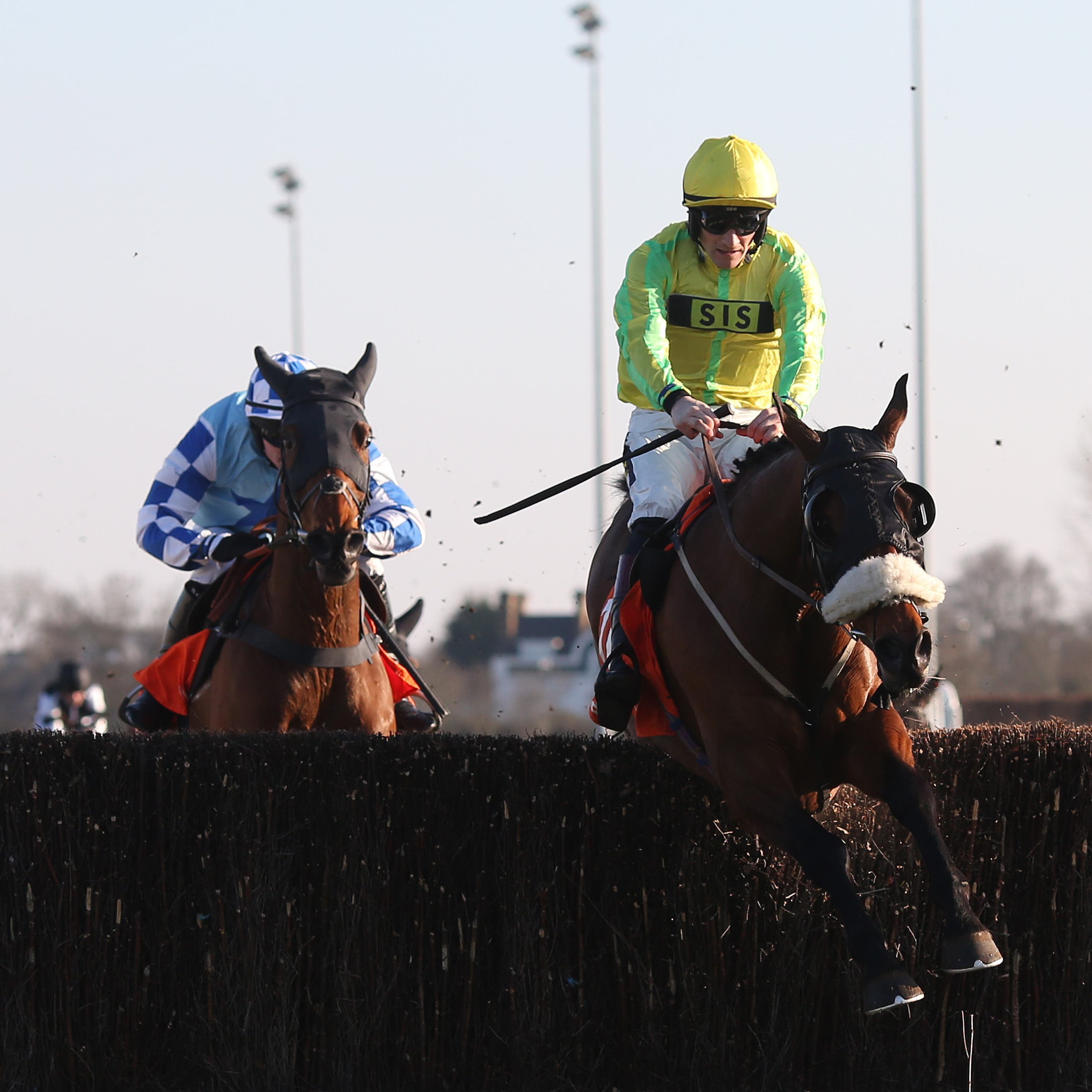 Walt and Sam Twiston-Davies clear the last fence ahead of Double Shuffle to win the 888Sport Handicap Chase at Kempton