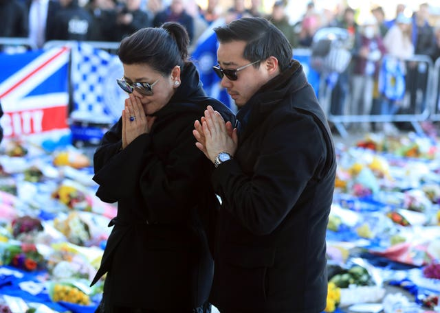 Aiyawatt Srivaddhanaprabha lays a wreath in memory of his father with his mother Aimon (Mike Egerton/PA)