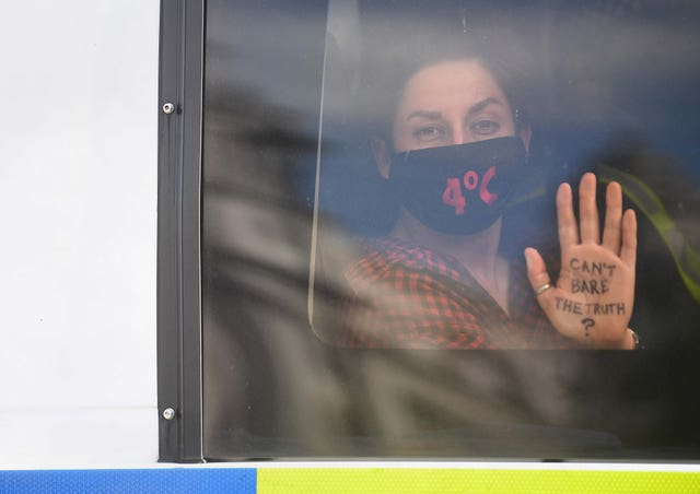 An Extinction Rebellion protester in a police van outside the Houses of Parliament