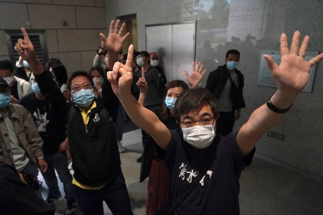 "Protesters gesture with five fingers, signifying the ""Five demands – not one less"" outside a court in Hong Kong (Kin Cheung/AP)"
