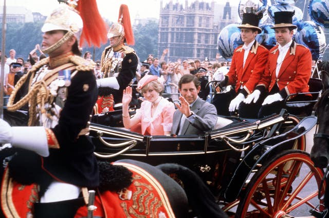 The newly married Prince and Princess of Wale wave to the London crowds from their open-top carriage as they make their way to Waterloo Station to depart for their honeymoon (PA)