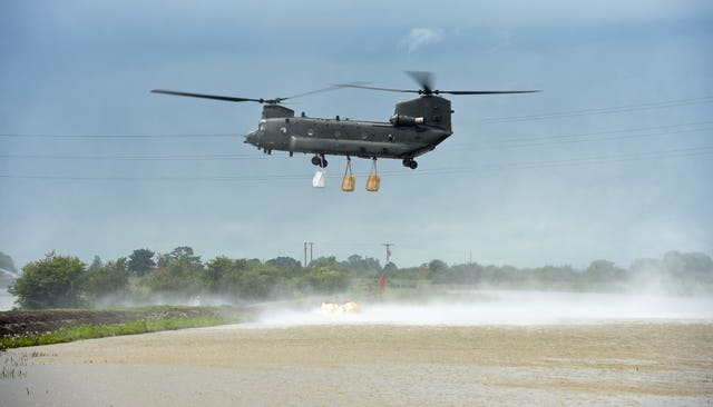 An RAF Chinook helicopter delivers sandbags to plug a gap in the River Steeping