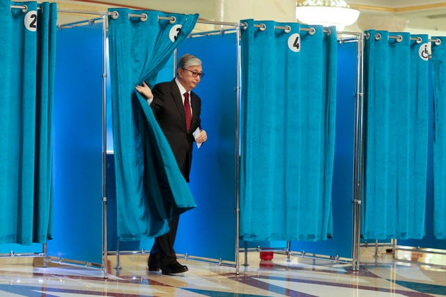 Kassym-Jomart Tokayev leaves a booth at a polling station