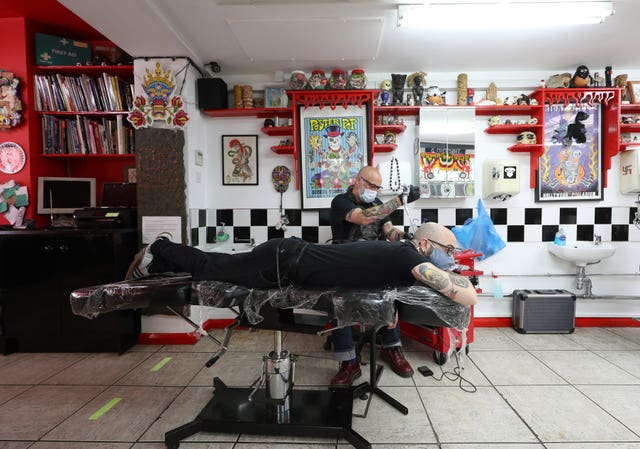 Tattoo artist Dale Frame gives his colleague Boris Di Prospero a swallow tattoo, at Flamin' Eight tattoo studio in Kentish Town, London