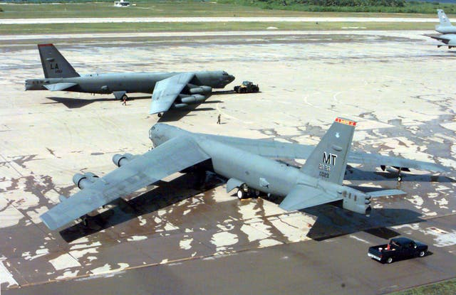A US Air Force B-52H Stratofortress being towed past another on the flight line at Navy Support Facility Diego Garcia