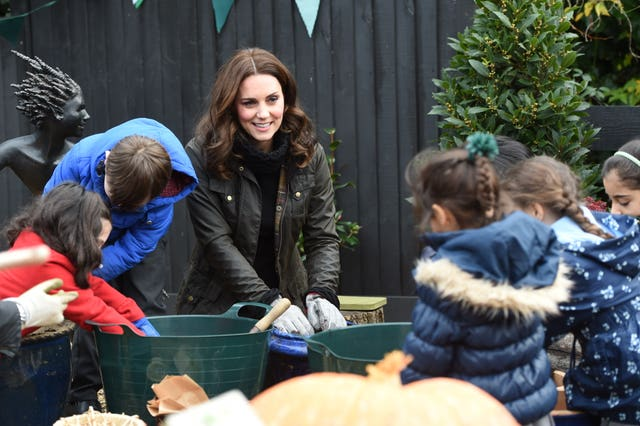 The Duchess of Cambridge planting bulbs during a visit to the Robin Hood Primary School (Eddie Mulholland/Daily Telegraph/PA)