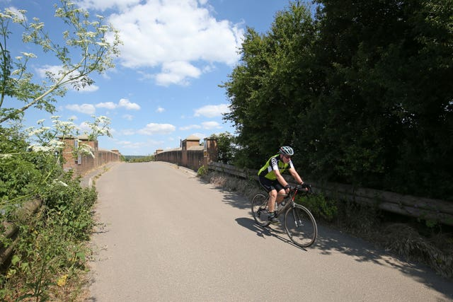 A cyclist crosses the railway bridge in White Waltham, Berkshire (Jonathan Brady/PA)