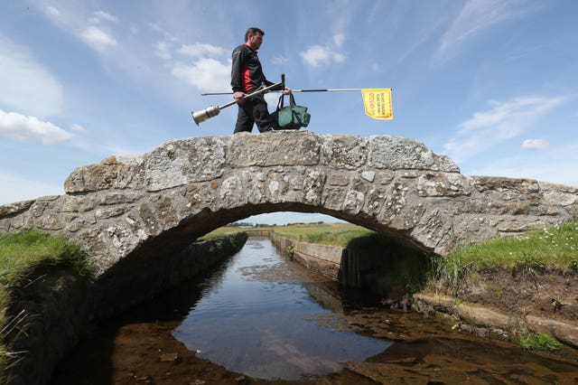 Greenkeeper Simon Connah crosses the Swilcan Bridge on the Old Course at St Andrews, in Fife