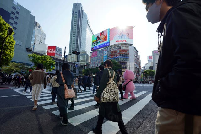 People wearing protective masks to help curb the spread of the coronavirus walk along a pedestrian crossing in Shibuya district in Tokyo