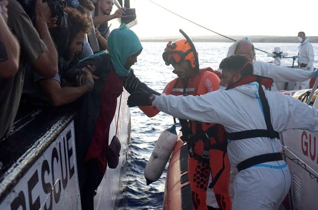 Migrants are evacuated by Italian coastguards from the Open Arms