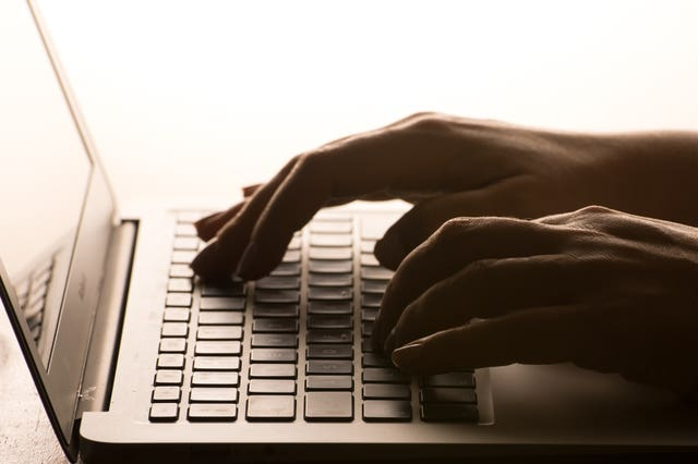 A woman's hands on a laptop keyboard