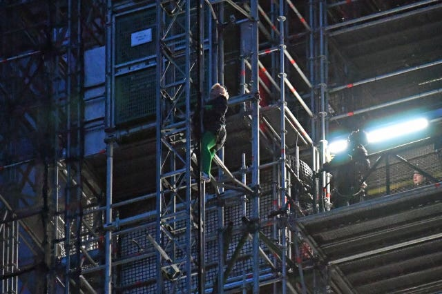 An Extinction Rebellion protester who has scaled the scaffolding surrounding Big Ben, at the Houses of Parliament, Westminster, London