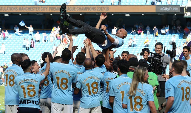 Pep Guardiola is thrown in the air by his Manchester City players after winning the Premier League in 2017-18