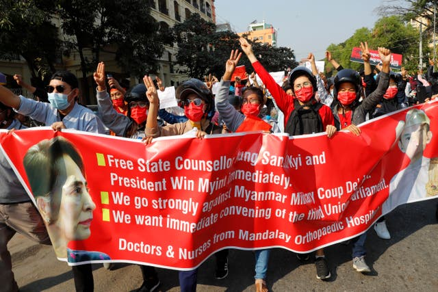 Protesters holding an image of deposed Myanmar leader Aung San Suu Kyi and President Win Myint in Mandalay