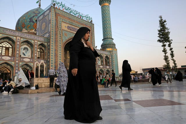 A head-to-toe veiled woman walks in the courtyard of the shrine of Saint Saleh in northern Tehran