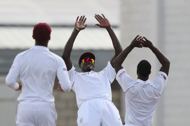 West Indies' captain Jason Holder, centre, celebrates with team-mate Kemar Roach