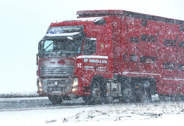 A lorry passes through heavy snow on the A66 in Durham, as heavy snowfall led to travel disruption (Owen Humphreys/PA)
