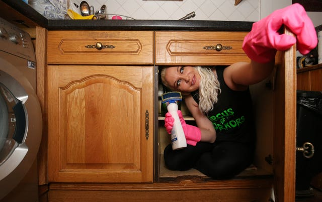 Circus contortionist Stephanie Bates squeezes herself into a kitchen cabinet at her home in London
