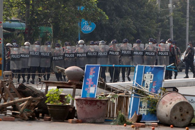 Myanmar riot police with shields move forward during a protest against the military coup in Mandalay, Myanmar