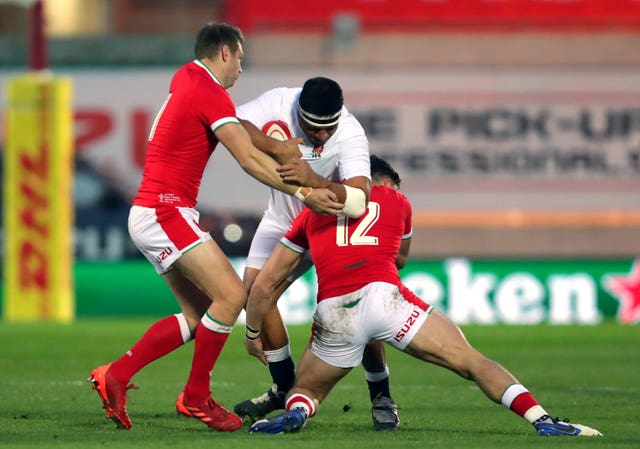 England's Mako Vunipola is tackled by Dan Biggar, left, and Johnny Williams