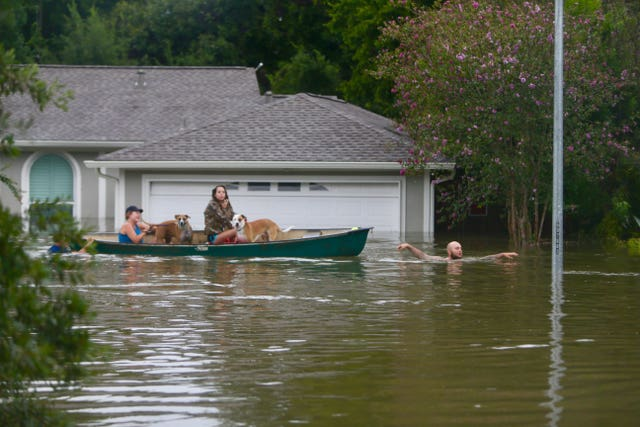 A family evacuates their Meyerland home in Houston complete with two dogs. (Mark Mulligan/AP)