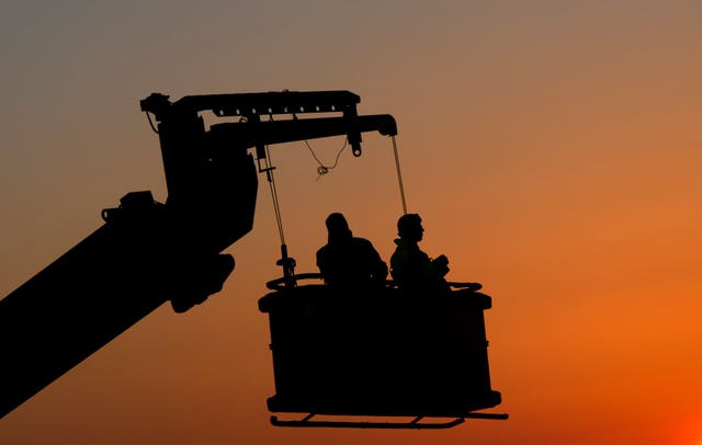Construction workers watch the sun set (Hannah McKay/PA)
