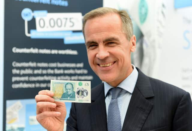 Governor of the Bank of England, Mark Carney, unveils the full design of the new polymer £5 note featuring Sir Winston Churchill (PA)