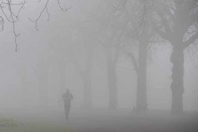 A jogger runs through a foggy Cannon Hill Park in Birmingham (Aaron Chown/PA)