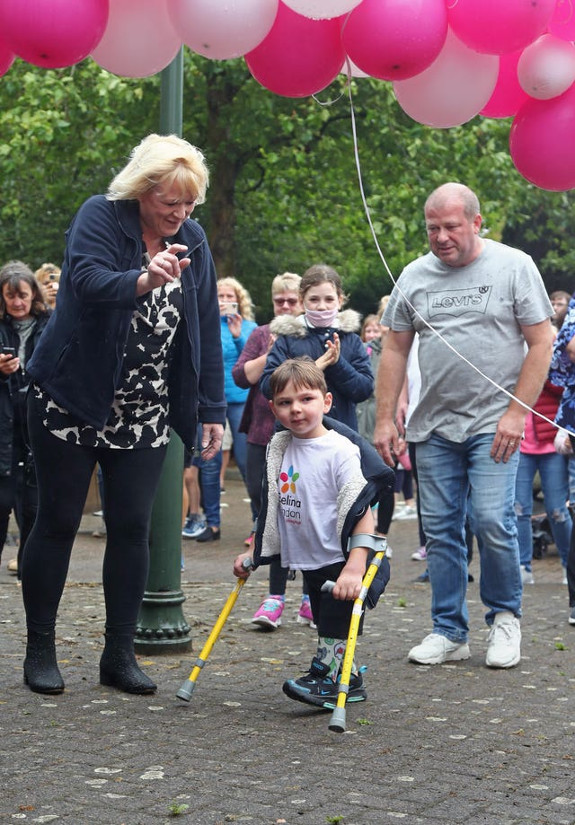 Tony Hudgell, who uses prosthetic legs, takes the final steps in his fundraising walk in West Malling, Kent, with mother Paula and father Mark