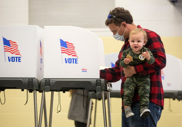 Tommy Tye celebrates his first birthday by accompanying his father Russell to vote at Alanton Elementary School in Virginia Beach, Virginia