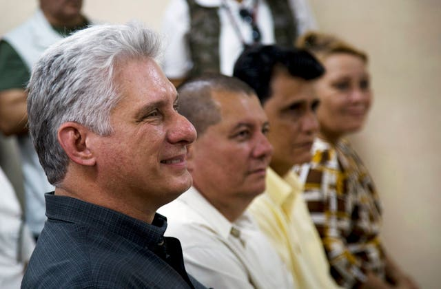 Cuba's president Miguel Diaz-Canel, left, attends a meeting in an art school during a tour in Las Tunas, Cuba