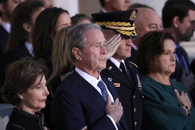 George W Bush watch as members of a military honour guard carry his father into the Capitol