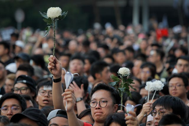 Protesters hold flowers to pay their respects to a man who fell to his death after hanging a protest banner