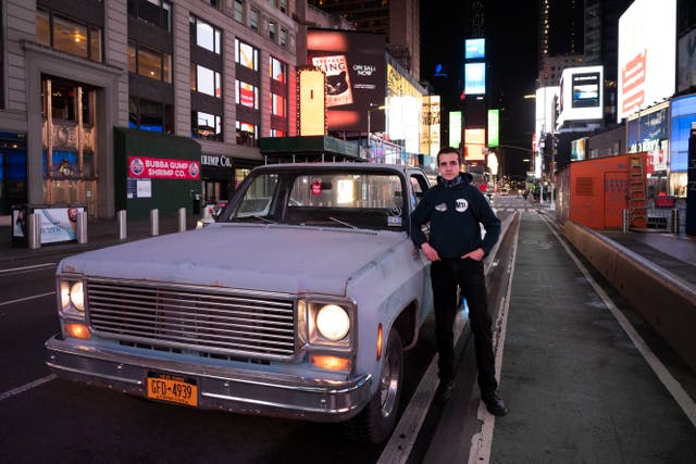 Mike Hodurski poses with his 1977 Chevy pickup in New York's Times Square during the coronavirus pandemic