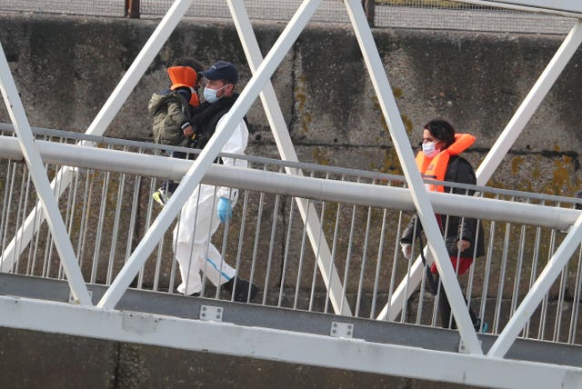 A group of people, including a child, thought to be migrants are brought into Dover, Kent