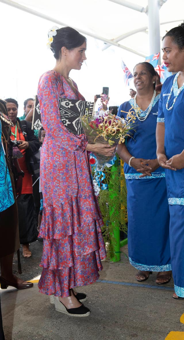 Meghan was given a bouquet of flowers during her visit to Suva Market