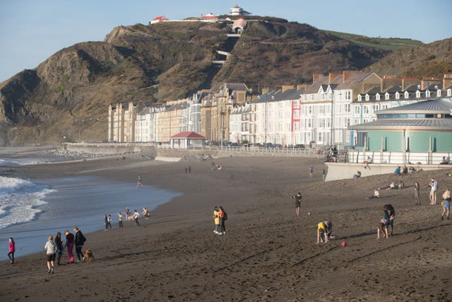 People enjoy the sunshine on Aberystwyth beach in Wales on Monday