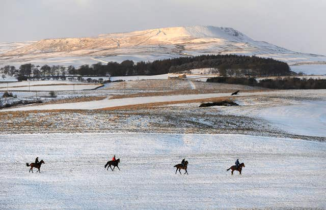 The Pennine hilltops are covered with snow as riders make their way onto the gallops at Middleham Moor near Leyburn (John Giles/PA)