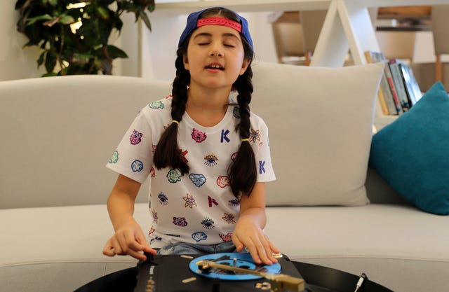 Michelle Rasul enjoys scratching her turntable in the lobby of her apartment building in Dubai, United Arab Emirates