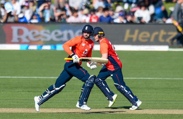 Eoin Morgan, right, and James Vince cross as they run a single