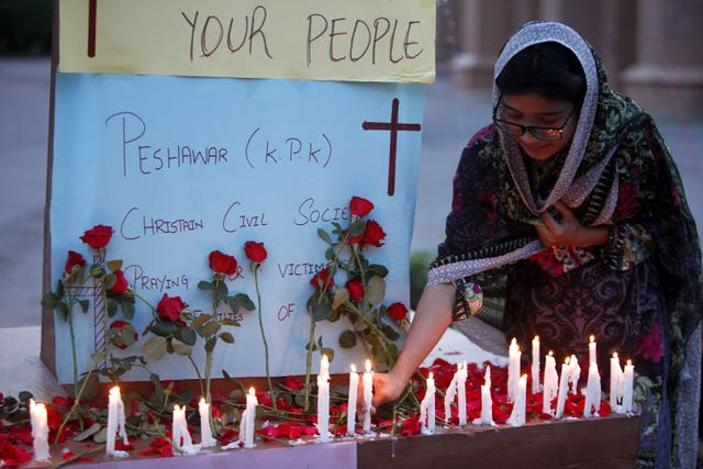 A woman lights a candle at a vigil for the victims of bomb explosions in churches and hotels in Sri Lanka