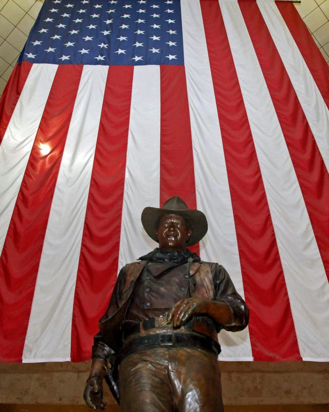 A bronze statue of late actor John Wayne stands before a four-storey high United States flag at John Wayne Orange County Airport in Santa Ana, California (Reed Saxon/AP)